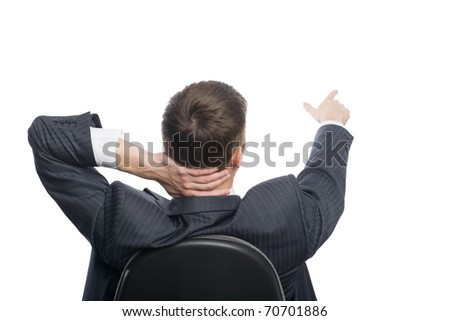 Young businessman sitting in an armchair shows his hand towards the. - stock photo