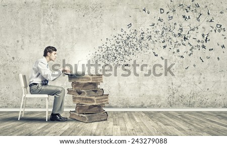 Young businessman sitting in chair and using laptop - stock photo