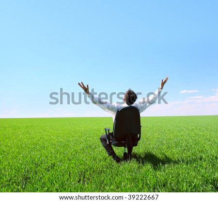 Young businessman sitting in chair on green field - stock photo