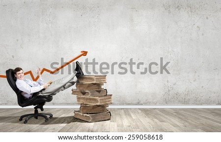 Young businessman sitting in chair with legs on pile of old books - stock photo