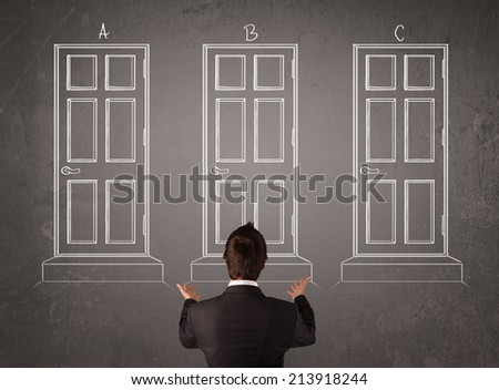 Young businessman sitting in front of a chalkboard and trying to choose the right door - stock photo