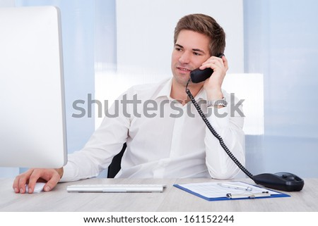 Young Businessman Sitting In Front Of Computer Talking On Telephone - stock photo