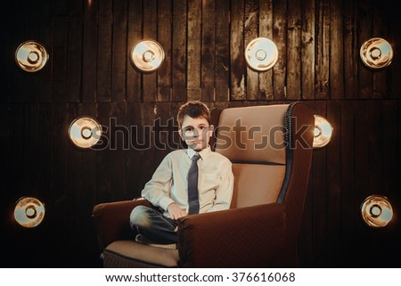 Young businessman sitting in front of lights wall