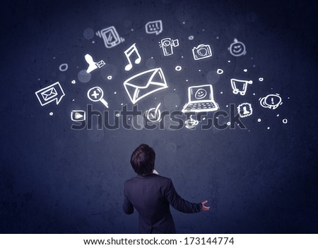 Young businessman sitting in office chair with sketched multimedia icons above his head - stock photo