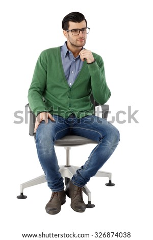 Young businessman sitting in swivel chair over white background, thinking. Full-length. - stock photo