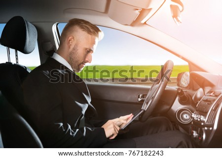 Young Businessman Sitting Inside Self Driving Car And Using Mobilephone