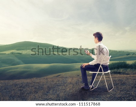Young businessman sitting on a chair on a green meadow and using a mobile phone - stock photo