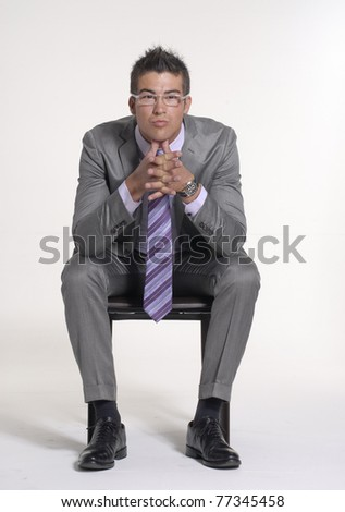 Young businessman sitting on a chair on white background. - stock photo