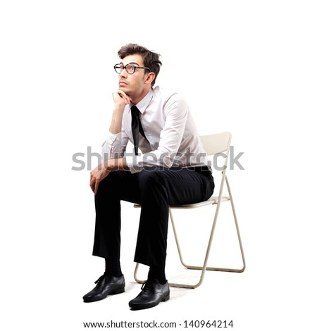 young businessman sitting on a chair thinking - stock photo