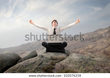 Young businessman sitting on a rock and triumphing with a laptop on his knees - stock photo