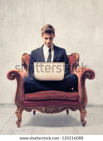 Young businessman sitting on a vintage armchair using a laptop computer - stock photo