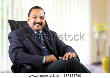 Young businessman sitting on chair at his office. - stock photo
