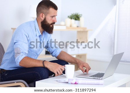 Young businessman sitting on chair in office - stock photo