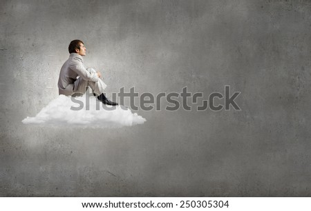 Young businessman sitting on cloud and relaxing - stock photo