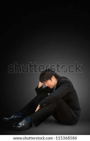 Young businessman sitting on floor with head down as if sad or depressed.