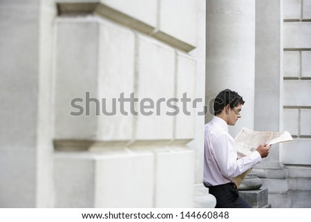 Young businessman sitting on pillar reading financial newspaper - stock photo