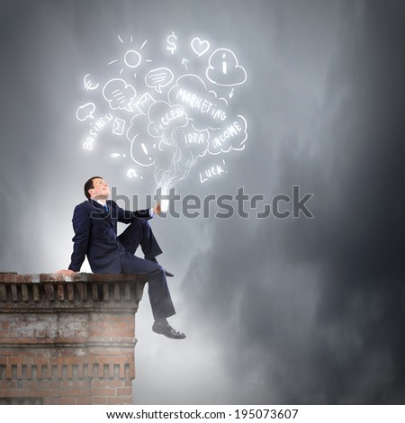 Young businessman sitting on roof of building