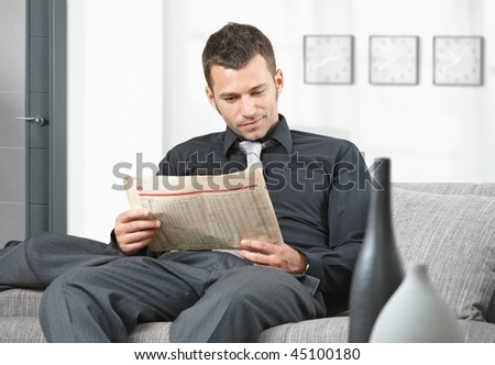 Young businessman sitting on sofa at office anteroom reading newspaper waiting. - stock photo