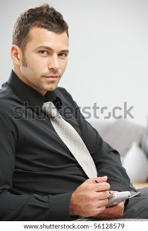 Young businessman sitting on sofa at office lobby using palmtop organizer. - stock photo