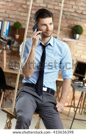 Young businessman sitting on swing in office, talking on mobilephone. - stock photo