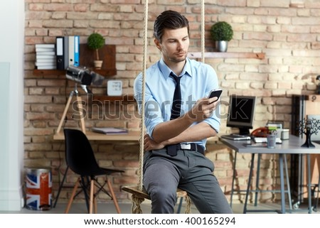 Young businessman sitting on swing, using mobilephone in modern office. - stock photo