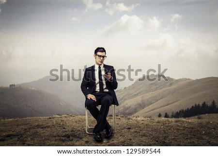 young businessman sitting on the chair in mountain