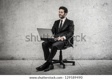 young businessman sitting on the chair with laptop