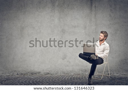 young businessman sitting on the chair with laptop on gray background