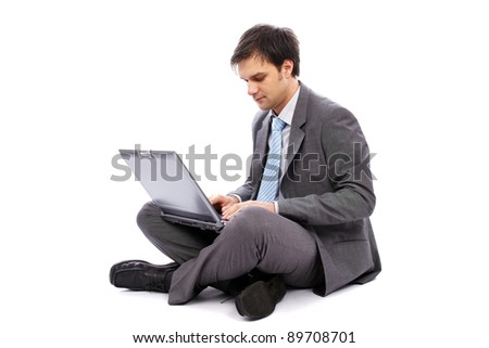Young businessman sitting on the floor and typing on a laptop