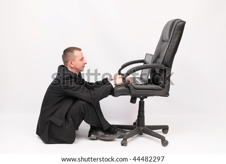 Young businessman sitting on the floor with notebook on the chair. Isolated o the white background. - stock photo