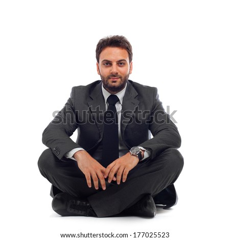 Young businessman sitting on the ground over white