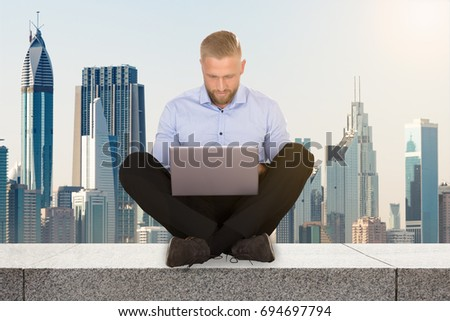 Young Businessman Sitting On The Rooftop Of A Skyscraper Using Laptop