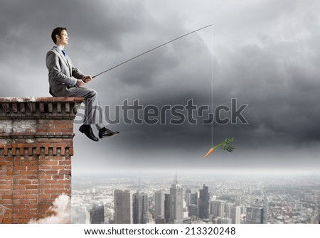 Young businessman sitting on top of building and fishing - stock photo