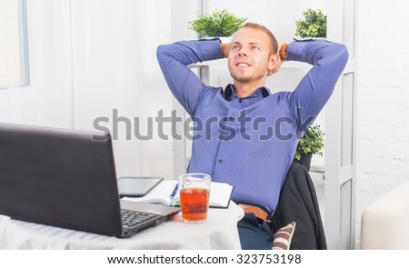 Young businessman sitting relaxed with his hands behind his head, dreaming, thinking or resting