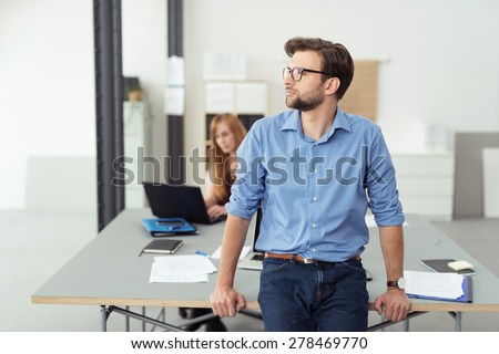 Young businessman sitting thinking balanced on the edge of his desk in the office staring pensively off to the left of the frame - stock photo