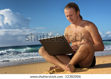Young businessman sitting with notebook on beach - closeup. Shot in Sodwana Bay nature reserve, KwaZulu-Natal province, Southern Mozambique area, South Africa.