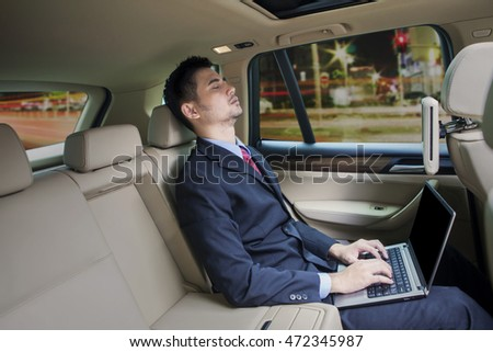 Young businessman sleeping in the car while using laptop computer