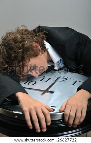 Young businessman sleeping on clock, deadline concept - stock photo