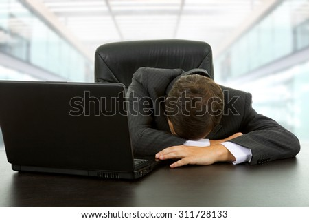 young businessman sleeping on the laptop at the office