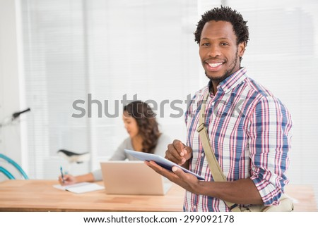 Young businessman smiling at the camera and businesswoman looking at the laptop in the backround in the office