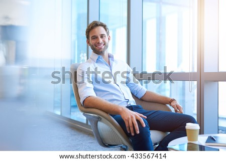 young businessman smiling at the camera while relaxing in a comfortable chair in a bright modern bright modern office space