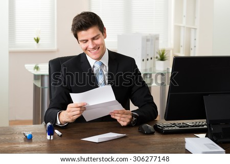 Young Businessman Smiling While Reading Paper At Desk In Office - stock photo