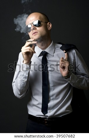 Young businessman smoking with coat on shoulder