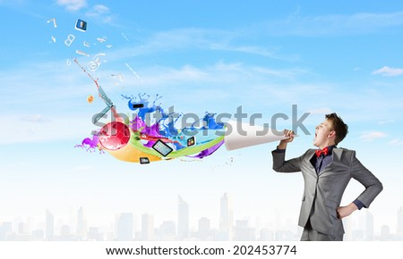 Young businessman speaking in trumpet and colorful splashes flying out - stock photo