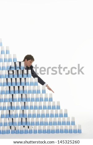 Young businessman stacking plastic cups into a pyramid against white background
