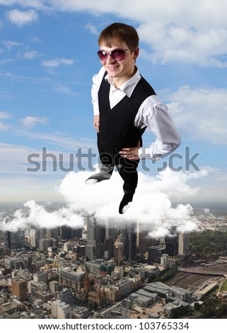 Young businessman standing against city andscape background - stock photo