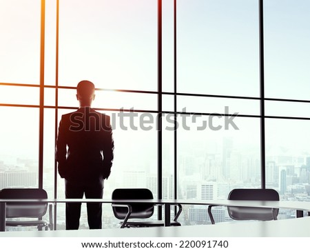 young businessman standing alone in big office - stock photo