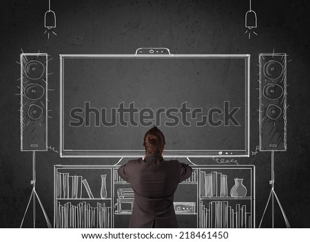 Young businessman standing and enjoying home cinema system sketched on a chalkboard - stock photo