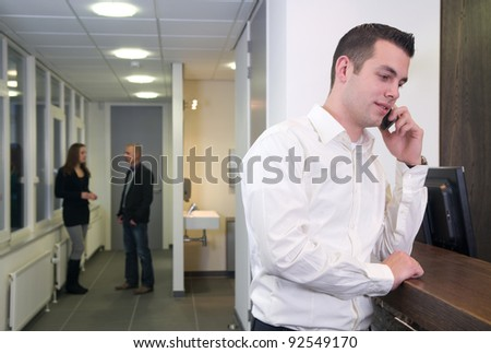 Young businessman standing at a desk with colleagues in the background - stock photo