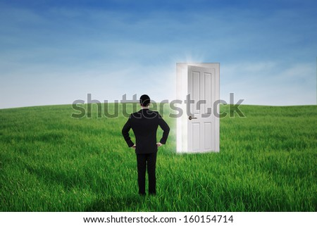 Young businessman standing at an opportunity door on the green meadow - stock photo
